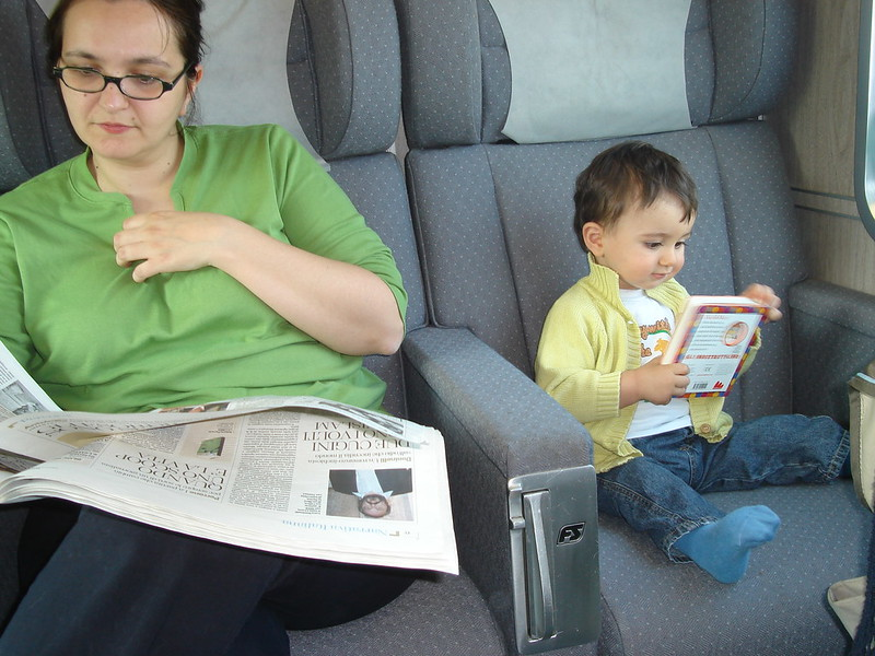 Francesca and her toddler son reading on a train