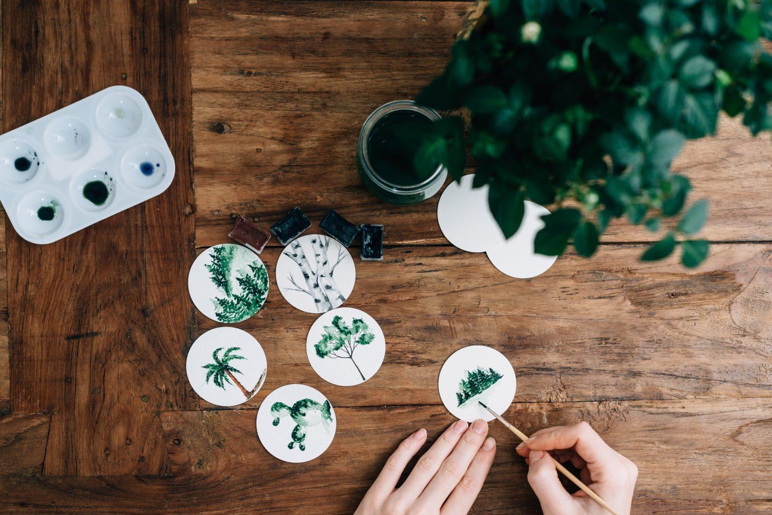 Mani che pitturano mini medaglioni con motivi floreali