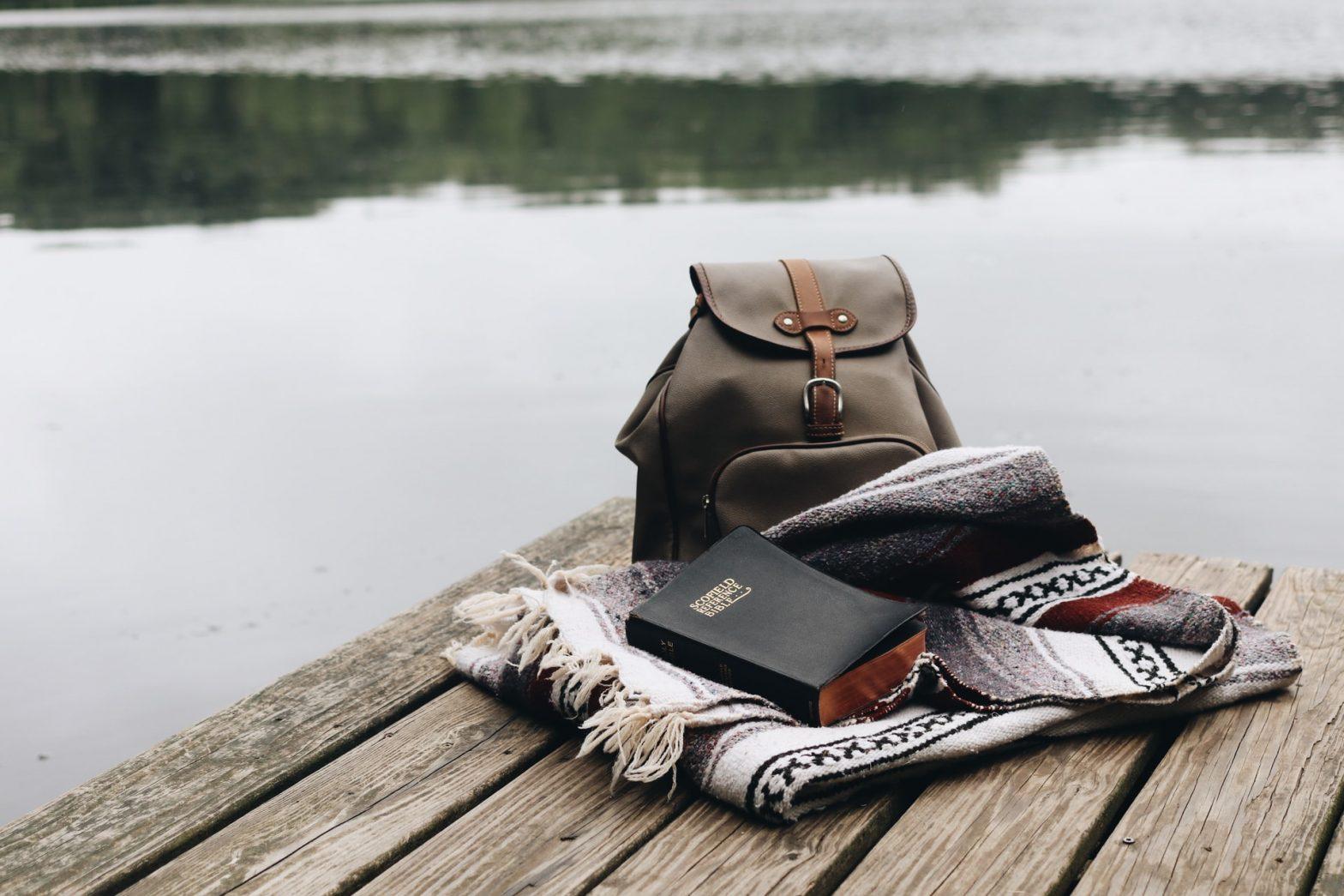 Zaino, coperta e quaderno su un molo sul lago