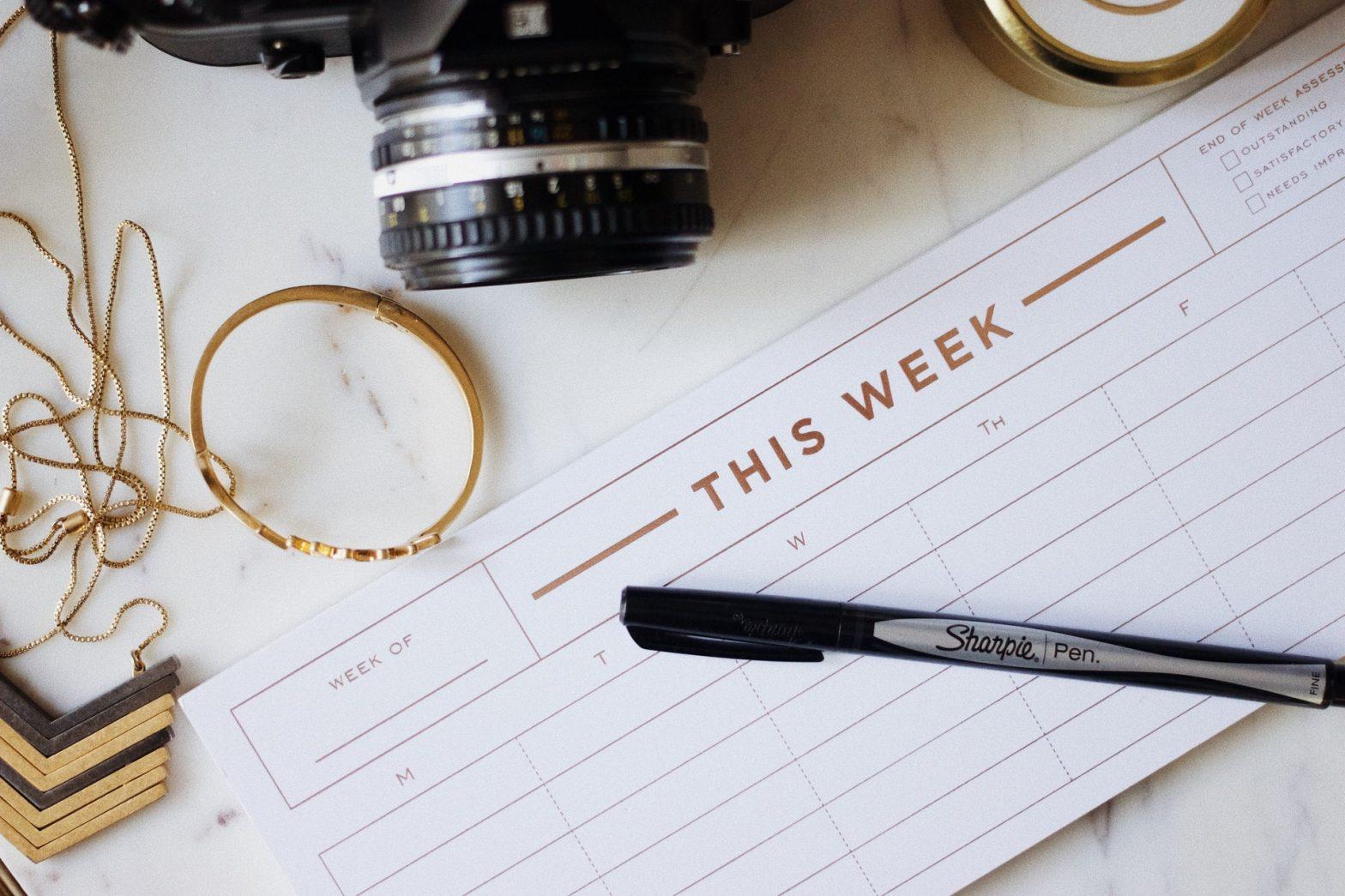 Planner settimanale con macchina fotografica su scrivania